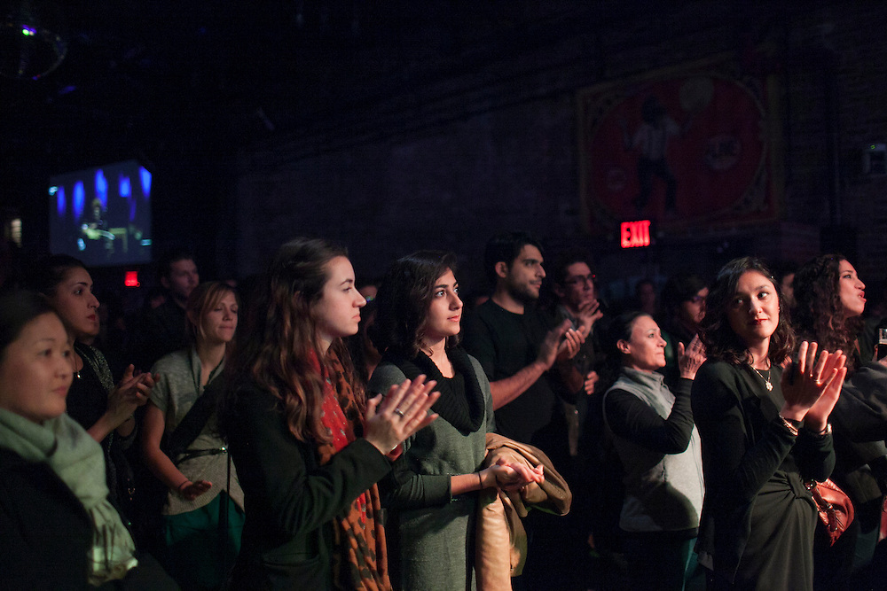 Spectators as Johnny Azari performs at a benefit concert for the Yellow Dogs, the band whose members were killed last week, at Brooklyn Bowl, 61 Wythe Avenue in the Williamsburg neighborhood of Brooklyn, NY on Monday, Nov. 18, 2013.<br /> <br /> Photograph by Andrew Hinderaker