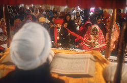 Bride; groom and priest at wedding ceremony in Patiala; Punjab; India,