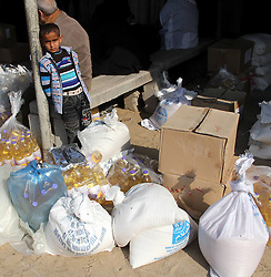 A Palestinian boy stands aside aid distributions at a UN food aid distribution centre in Rafah, southern Gaza Strip, January 2, 2013. Photo by Imago / i-Images...UK ONLY