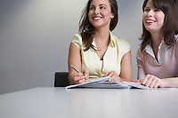 Two women sitting at table with paperwork looking up and smiling