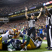 Side Judge Lance Easley, center, looks at back judge Derrick Rhone-Dunn as Easley calls a Seattle Seahawks touchdown catch by Golden Tate and Rhone-Dunn says the catch is no good in the final second of the Seattle Seahawks and Green Bay Packers game Monday Night Football game on September 24, 2012 at CenturyLink FIeld in Seattle. The controversial call put the Seahawks over the Packers to win 14 to 12. (Joshua Trujillo, seattlepi.com)