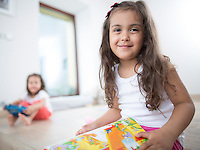 Portrait of cute girl holding book with sister in background at home