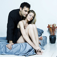 beautiful young caucasian couple in a bed on isolated background