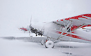 Alaska. Anchorage. Merrill Field. Piper J3 Cub is in the foreground of this snowy line-up.  Winter snow squalls limit visibility and ground small planes.