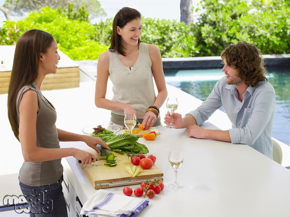 Three young adult friends preparing a salad while drinking wine and laughing on patio