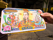 "10 AUGUST 2014 - BANGKOK, THAILAND:     A man holds a stack of Hell Money before tossing it into a burn barrel in Bangkok for Ghost Month. Hell money is a form of joss paper printed to resemble legal tender bank notes and is used in religious ceremonies in Chinese communities. The seventh month of the Chinese Lunar calendar is called ""Ghost Month"" during which ghosts and spirits, including those of the deceased ancestors, come out from the lower realm. It is common for Chinese people to make merit during the month by burning ""hell money"" and presenting food to the ghosts.   PHOTO BY JACK KURTZ"