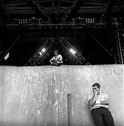 Donovan Philips Leitch performing while a fan stands against & below the stage at Glastonbury, 1989.