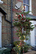 A tree dressed with Christmas decorations sits outside a Victorian terraced house in Herne Hill, SE24, on 18th December 2017, in London, England.