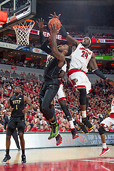 Louisville forward Montrezl Harrell, right, and forward/center Mangok Mathiang contest a shot by Pittsburgh guard/forward Chris Jones in the second half. <br /> <br /> The University of Louisville hosted the University of Pittsburgh, Wednesday, Feb. 11, 2015 at Yum Center in Louisville. <br /> <br /> Photo by Jonathan Palmer