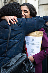 © Licensed to London News Pictures. 27/02/2020. London, UK. Friends of the Earth lawyer Katie de Kauwe (R) hugs a friend while holding a copy of the legal ruling outside the High Court after judges ruled that the planned expansion of Heathrow Airport was illegal over climate change. Photo credit: Rob Pinney/LNP