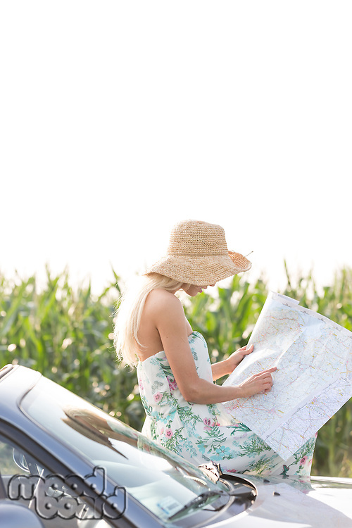 Woman reading map while leaning on convertible