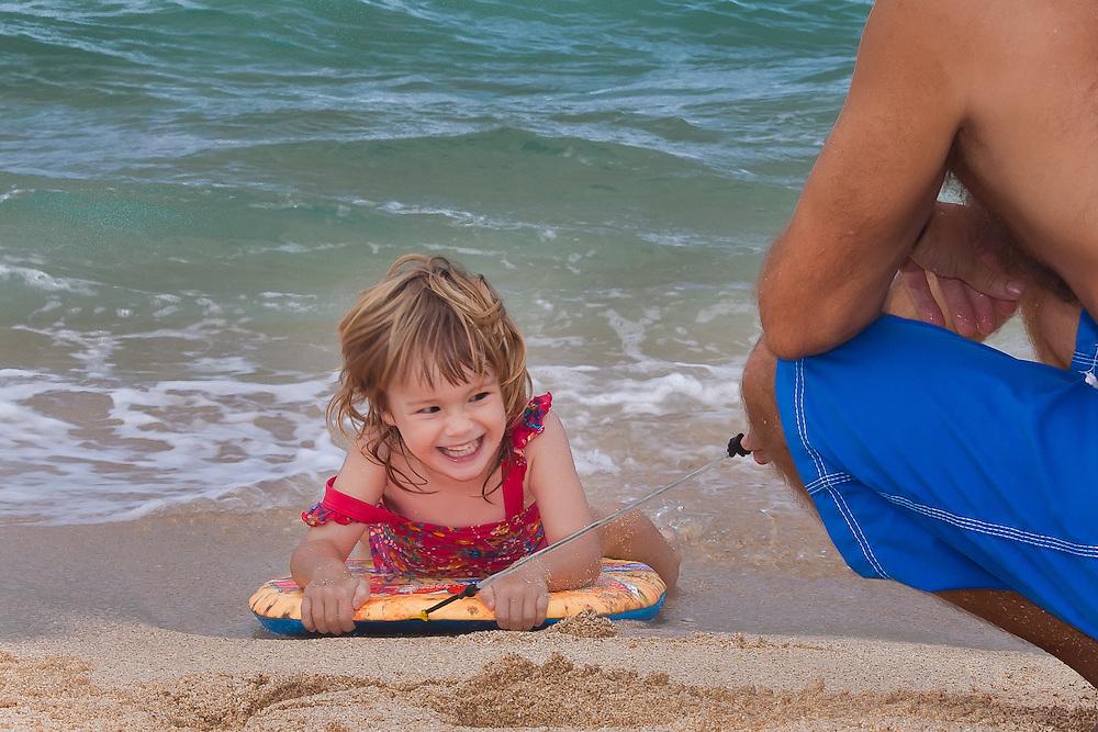 A little girl on a boogie board on the beach in Hawaii