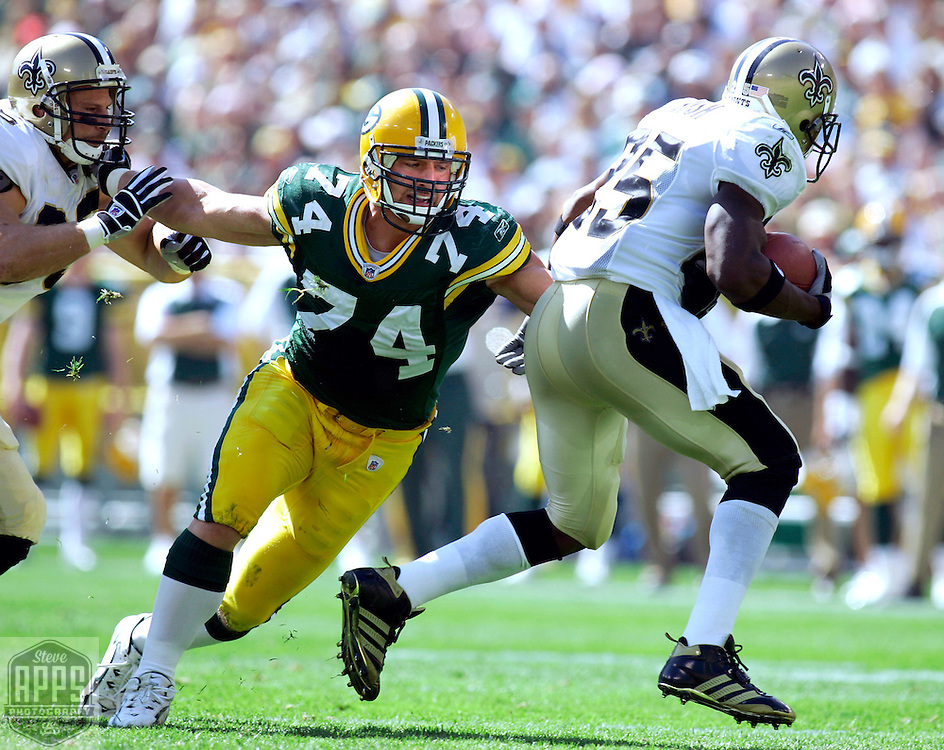 Green Bay's Aaron Kampman sheds a block from New Orleans Ernie Conwell to tackle Reggie Bush for a 1-yard loss in the 1st quarter. .The Green Bay Packers hosted the New Orleans Saints at Lambeau Field Sunday September 17, 2006. Steve Apps-State Journal.