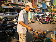 25 FEBRUARY 2015 - PHNOM PENH, CAMBODIA: A street food vendor grills pork sticks, called satay, in a market in Phnom Penh.      PHOTO BY JACK KURTZ