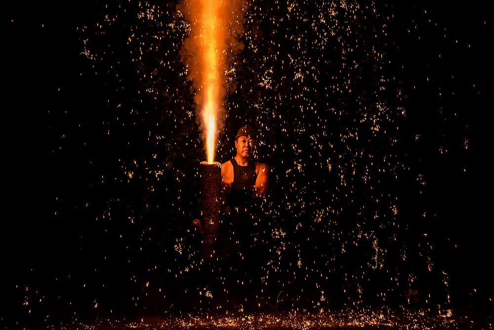 A man launches handheld fireworks, known as tezutsu hanabi, during a spring festival at Matsudaira Tosho-gu, a Shinto shrine in Toyota, Japan.