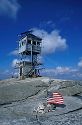 The fire tower on the summit of Mt. Cardigan in Mt. Cardigan State Park.  American flag.  Alexandria, NH