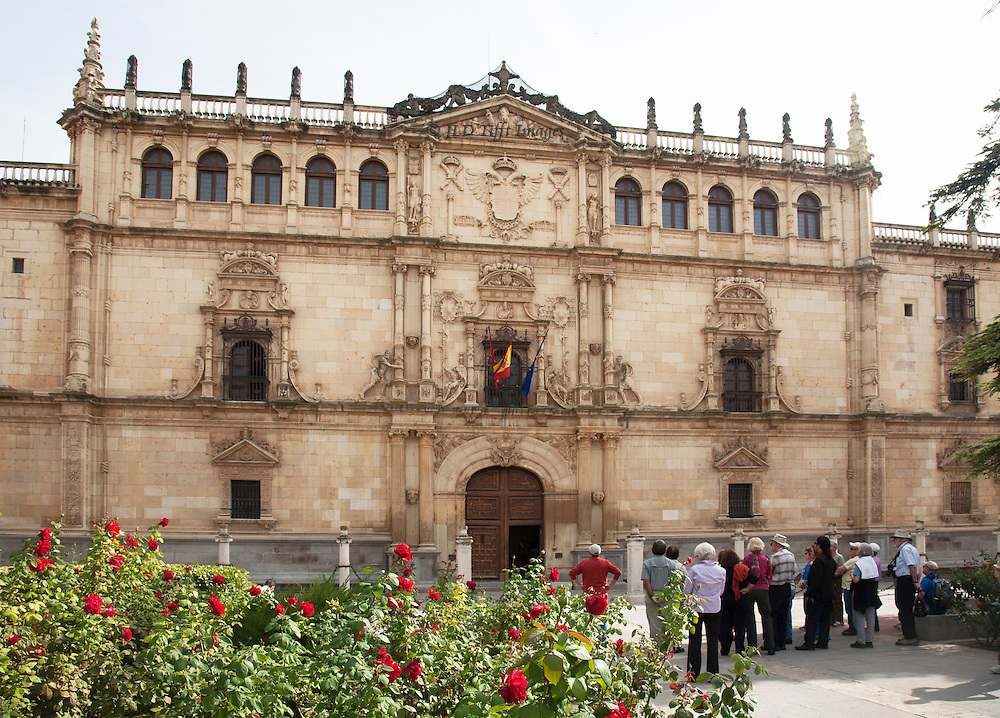 Facade of the university College of Ildefonso at Alcala de Henares.  Flourish of red roses in the foreground, and a clutch of tourists lined up admiring the building's Plateresque ornamental flourishes around its doors and windows.  The building dates from the turn of the 15th-16th century.  The university, founded by Ximenez de Cisneros, opened in 1508 as the College of St. Ildefonso.  The facade was designed by Rodrigo Gil de Hontanon in the style known as plateresque.