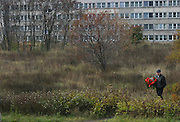 A man takes a shortcut through a field carrying flowers to the cemetery on All Saints Day. Lodz, Poland.