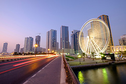 Evening view of Eye of the Emirates ferris wheel  at Al Qasba and skyline of Sharjah United Arab Emirates