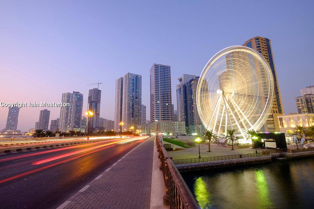 Evening view of Eye of the Emirates ferris wheel  at Al Qasba and skyline of Sharjah United Arab Emirates