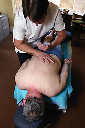 Chiropractor adjusting cervical spine on patient,