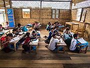 06 NOVEMBER 2014 - SITTWE, RAKHINE, MYANMAR: A school for Rohingya Muslim children in an IDP camp. After sectarian violence devastated Rohingya communities and left hundreds of Rohingya dead in 2012, the government of Myanmar forced more than 140,000 Rohingya Muslims who used to live in and around Sittwe, Myanmar, into squalid Internal Displaced Persons camps. The government says the Rohingya are not Burmese citizens, that they are illegal immigrants from Bangladesh. The Bangladesh government says the Rohingya are Burmese and the Rohingya insist that they have lived in Burma for generations. The camps are about 20 minutes from Sittwe but the Rohingya who live in the camps are not allowed to leave without government permission. They are not allowed to work outside the camps, they are not allowed to go to Sittwe to use the hospital, go to school or do business. The camps have no electricity. Water is delivered through community wells. There are small schools funded by NOGs in the camps and a few private clinics but medical care is costly and not reliable.   PHOTO BY JACK KURTZ