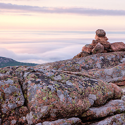 A cairn, above the fog, marks a hiking trail on the summit of Cadillac Mountain in Maine's Acadia National Park.