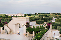 "FASANO, ITALY - 22 JULY 2018: Hotel guests walk out of Borgo Egnazia, a high-end resort in Puglia, on Italy's eastern coast, in Fasano, Italy, on July 22nd 2018.<br /> <br /> Borgo Egnazia, modeled after a 15th century Apulian village, rolls out over 250 acres on a plot of land originally razed by Mussolini and intended as an air force base, ending nearing the Adriatic. Aldo Melpignano, the 40 years old owner, has pioneered a hospitality company that has managed to seize on the hype surrounding wellness and authentic experiences at once. His company, SD Hotels, turns Puglia's traditional farmhouses into resorts that focus on fitness (Apulian folk dance classes in 400 year old olive groves) and otherworldly spa treatments (one massage uses ""vibrational water"") in addition to traditional Italian fare (milk serum, handmade orecchiette pasta, octopus in a broth of just-plucked tomatoes). <br /> <br /> Borgo Egnazia is the largest of his five properties, with three public pools, a village square out of central casting, and nearly 200 rooms.  Celebrities like Madonna have been won over by Borgo Egnazia's faux Medieval facades and farmhouse chic interiors, an effect best described as ""Game of Thrones"" meets Restoration Hardware. Justin Timberlake and Jessica Biel got married here in 2012. SD Hotels, which last year saw revenues of $57 million, started with his family's summer home, Masseria San Domenico, a few miles down the road from Borgo Egnazia."