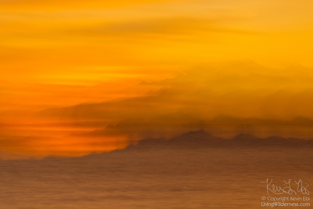 Camera movement during a long exposure creates an impressionistic stacked view of the Olympic Mountains over Puget Sound in this view from Edmonds, Washington.