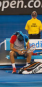Bernard Tomic (AUS) faced R. Nadal (ESP) in day two play of the 2014 Australian Open at Melbourne's Rod Laver Arena. Here, Tomic is sullen after he forfeited the match blaming leg pain giving Nadal the win. One set was completed during match play with Nadal up 6-4.