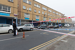 © Licensed to London News Pictures. 03/04/2017. LONDON, UK.  A police officer stands at the crime scene and police cordon around BJ Wines in Freemasons Road, Canning Town, east London. Ahmed Jah, 21 is reported to have been knifed inside the off license, BJ Wines in Freemasons Road yesterday afternoon after he was set upon by a gang of men and stabbed in the chest. Emergency ambulance services attended and the man was pronounced dead at the scene shortly after.  Photo credit: Vickie Flores/LNP