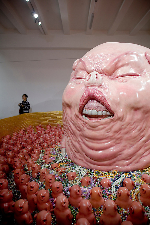 """Visitors to Chen Wenling's exhibition called """"The God of materialism"""" look at a sculpture on display at an art gallery in Beijing fashionable 798 art district."""