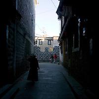 LHASA, JUNE-16, 2009 : an elderly Tibetan woman walks in an alley in the Tibetan district in the evening.