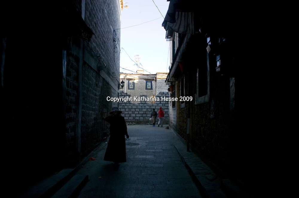 LHASA, JUNE-16, 2009 : an elderly Tibetan woman walks in an alley in the Tibetan district in the evening.