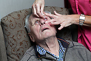 wet eye dripping of elderly man by nurse
