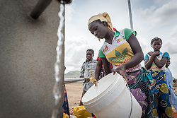 30 May 2019, Mokolo, Cameroon: A young woman waits for her bucket to fill up at one of the tapstands in Minawao camp. The Minawao camp for Nigerian refugees, located in the Far North region of Cameroon, hosts some 58,000 refugees from North East Nigeria. The refugees are supported by the Lutheran World Federation, together with a range of partners.