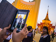 "31 JANUARY 2013 - PHNOM PENH, CAMBODIA: A person takes a photo of Norodom Sihanouk's crematorium at the National Museum in Phnom Penh. Norodom Sihanouk (31 October 1922 - 15 October 2012) was the King of Cambodia from 1941 to 1955 and again from 1993 to 2004. He was the effective ruler of Cambodia from 1953 to 1970. After his second abdication in 2004, he was given the honorific of ""The King-Father of Cambodia."" Sihanouk served two terms as king, two as sovereign prince, one as president, two as prime minister, as well as numerous positions as leader of various governments-in-exile. He served as puppet head of state for the Khmer Rouge government in 1975-1976. Most of these positions were only honorific, including the last position as constitutional king of Cambodia. Sihanouk's actual period of effective rule over Cambodia was from 9 November 1953, when Cambodia gained its independence from France, until 18 March 1970, when General Lon Nol and the National Assembly deposed him. Upon his final abdication, the Cambodian throne council appointed Norodom Sihamoni, one of Sihanouk's sons, as the new king. Sihanouk died in Beijing, China, where he was receiving medical care, on Oct. 15, 2012. His funeral procession, which will wind through Phnom Penh is Friday, Feb.1 and his cremation is on Feb. 4, 2013. Over a million people are expected to attend the service.     PHOTO BY JACK KURTZ"