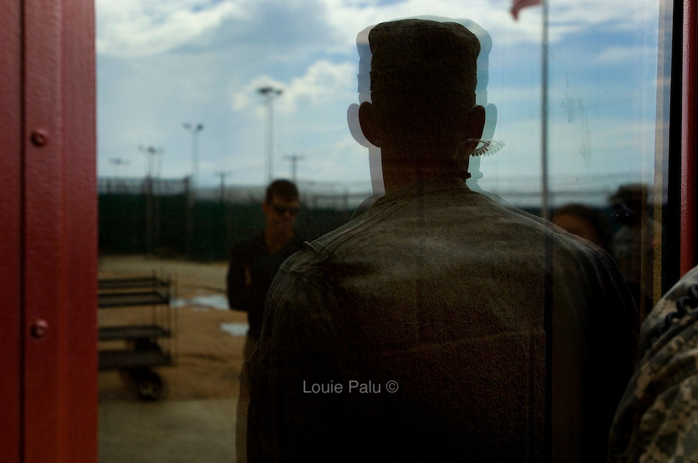 """A member of the U.S. military is seen reflected in the window at the entrance to Camp 6, the newest camp used as a maximum security facility to hold detainees at the Guantanamo Bay detention facility. The U.S. Government is currently holding approximately 340 """"enemy combatants"""" in Guantanamo Bay, Cuba. They were captured during the """"Global War on Terrorism"""" after the attacks on the United States on September 11, 2001. This photo was reviewed by a U.S. Military official before transmission."""