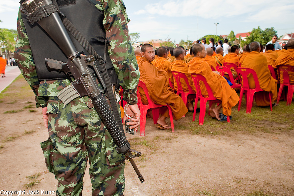 """Sept. 26, 2009 -- PATTANI, THAILAND:  A Thai soldier guards Buddhist monks during the Tak Bat Sankatan ceremony in Pattani Saturday. The Thai army has a large presence at these gatherings because the monks been targets of assassination by Muslim extremists battling the Thai government. Buddhists in Thailand's three southern most provinces gathered in Pattani Saturday, Sept 26 to celebrate Tak Bat Sankatan, the day Lord Buddha returned to earth and was greeted by a crawd of his disciples and Buddhist believers who were waiting to offer him food. Buddhists monks representing the 266 """"Wats"""" (temples) in the three provinces (Pattani, Narathiwat and Yala) processed through the crowd and were presented with food and gifts.   Photo by Jack Kurtz"""