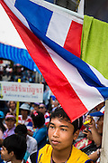 15 FEBRUARY 2014 - BANGKOK, THAILAND: An anti-government protestor sits under a Thai flag at the Chaeng Watthana stage of the anti-government Shutdown Bangkok protests. The protests, organized by the  People's Democratic Reform Committee (PDRC), have tried to shutdown the Thai capital but crowds at the venues are getting smaller and police have taken back a couple of protest sites.     PHOTO BY JACK KURTZ