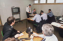 Police officers working at desks in police station briefing room,