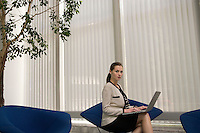 Business woman using laptop in office lobby portrait