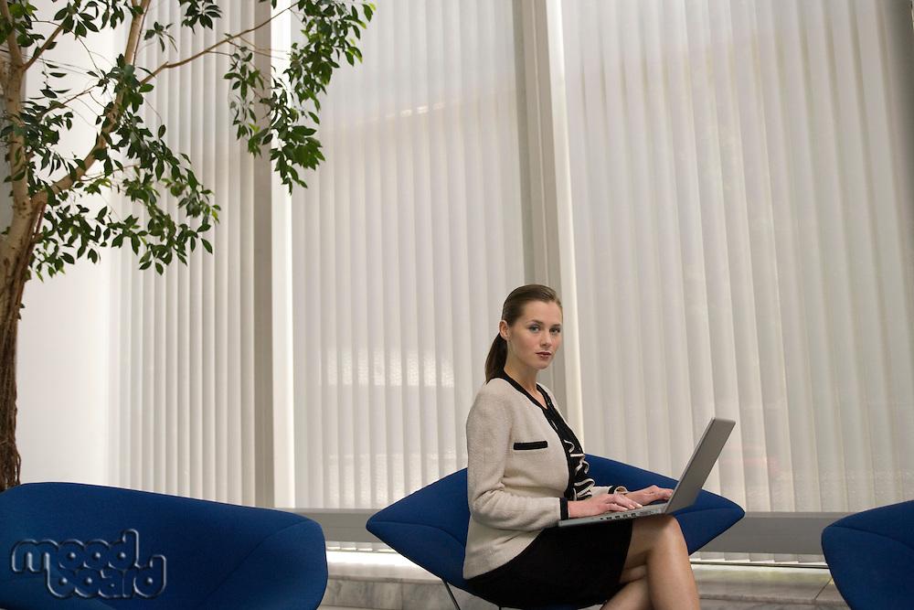 Business woman using laptop in office lobby portrait
