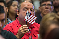 A U.S. citizen applicant holds and American flag during a naturalization ceremony at the Evo A. DeConcini U.S. Courthouse in Tucson, Arizona, U.S., on Friday, Sept. 16, 2016. Photographer: David Paul Morris/Bloomberg
