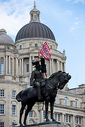 LIVERPOOL, ENGLAND - Friday, June 26, 2020: A man climbs on top of a statue of King Edward VII as Liverpool supporters celebrate their team's Premier League title victory at the Pier Head, Liverpool. With government COVID-19 restrictions in place the games have been played behind closed doors without fans. Liverpool won their 19th top-flight Championshop with seven games of the seaosn left, a record, it was the club's first title in 30 years and the first of the FA Premier League era. (Pic by David Rawcliffe/Propaganda)