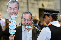 © Licensed to London News Pictures. 20/10/2018. LONDON, UK. A Nigel Farage mask wearer meets a police officer.  Thousands of people take part in a demonstration, organised by the People's Vote campaign, beginning with a march from Park Lane to a rally in Parliament Square.  The People's Vote seeks a referendum on the outcome of the final Brexit negotiations ahead of 29 March 2019, the date that the UK is due to leave the EU.  Photo credit: Stephen Chung/LNP