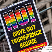 "Anti Trump demonstrators holding rainbow sign ""NO! Drive Out Trump/Pence Regime"" RefuseFascism.org during NYC Pride March."