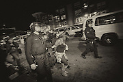 A woman is arrested and escorted to a transportation bus in Oakland.