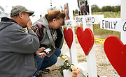 Lorenzo Flores (L) and Terrie Smith react at a line of crosses in remembrance of those killed in the shooting at the First Baptist Church of Sutherland Springs, Texas, U.S.  November 9, 2017.  REUTERS/Rick Wilking