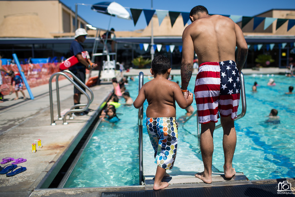 Visitors enjoy swimming, music, and balloon animals during the Waving the Red, White & Blue Pool Party at the Milpitas Sports Center in Milpitas, California, on July 4, 2014. (Stan Olszewski/SOSKIphoto)